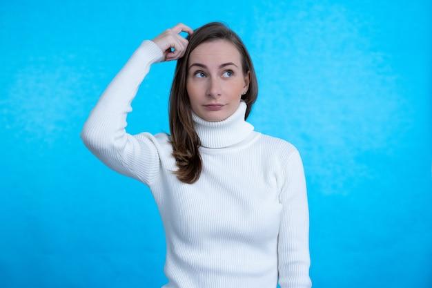 孤立した青い壁に頭を掻きながら疑問を持っている女性。