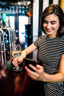 Woman having a drink and using smartphone in a bar