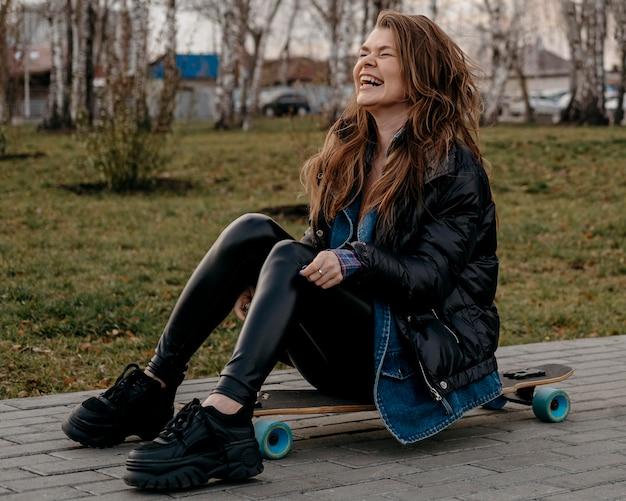 Donna che ha divertimento all'aperto con lo skateboard