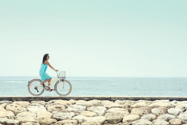 Женщина с удовольствием езда на велосипеде на пляже