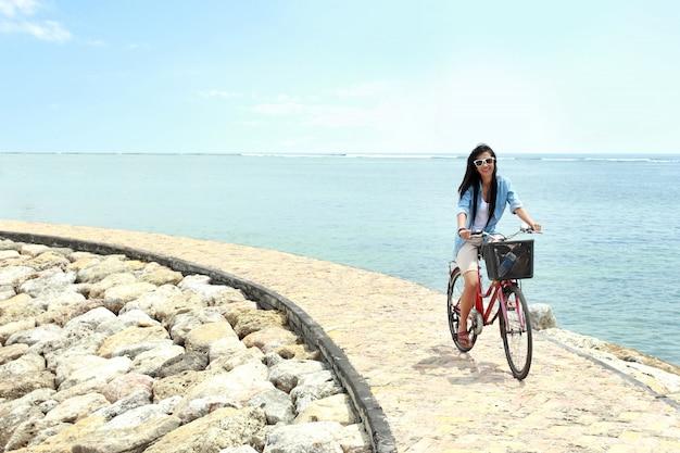 ビーチで自転車に乗って楽しんでいる女性
