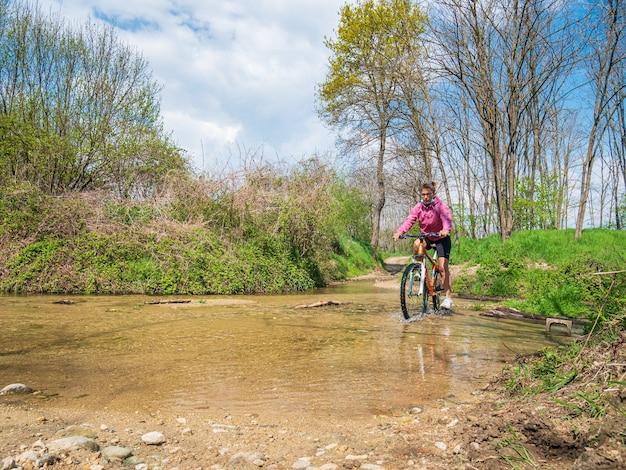 緑の森の風景の中で川を渡るマウンテンバイクに乗って楽しんでいる女性
