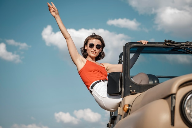 Женщина, весело путешествуя на машине