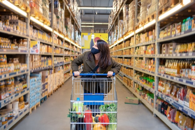 Woman having fun while do grocery shopping. covid medical mask copy space