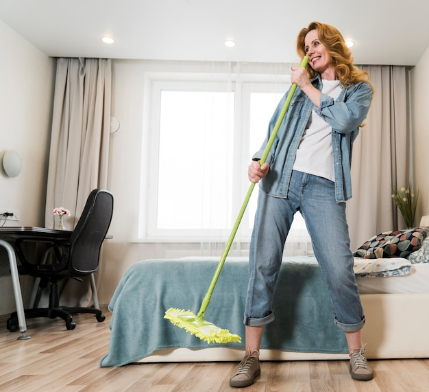 Woman having fun while mopping the floor