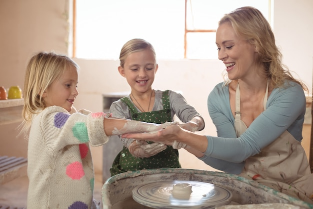 Woman having fun with girls while making pottery