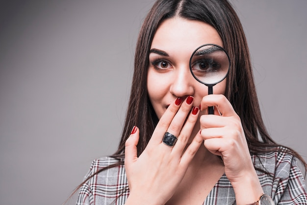 Woman having fun with magnifying glass