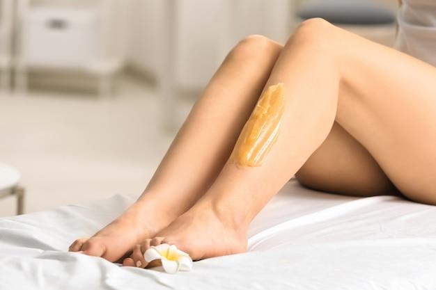 Женщина, имеющая процедуру удаления волос на ноге с помощью шугаринговой пасты в салоне