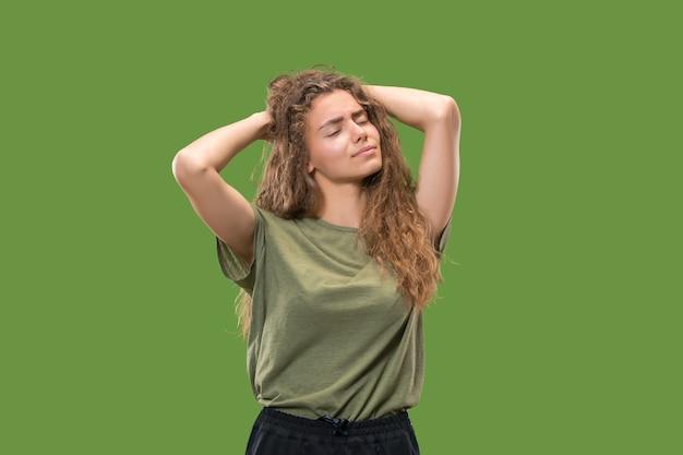 Женщина, имеющая головную боль, изолированную над зеленой стеной.