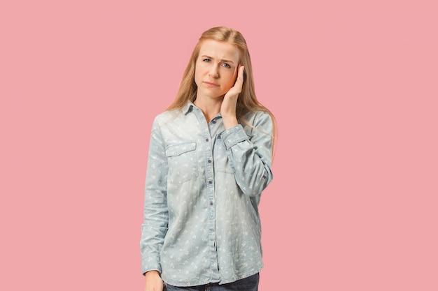 頭痛を持つ女性。ピンクの背景に分離。
