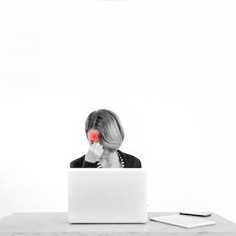 ラップトップで作業中に頭痛を持つ女性