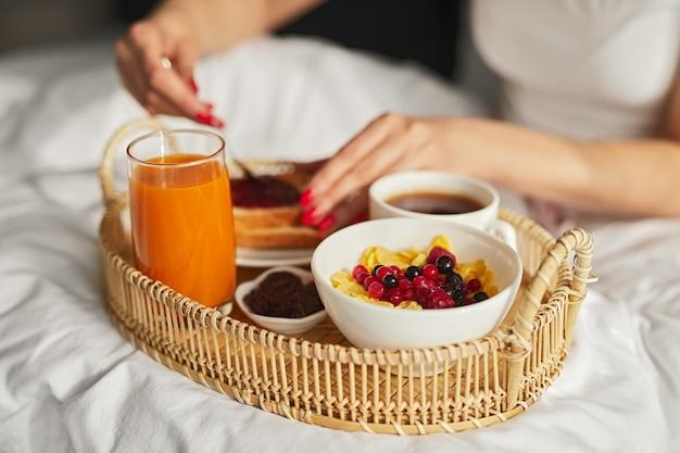 ベッドで健康的な朝食をとっている女性