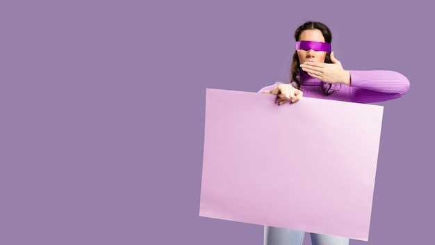Woman having her eyes tied holding an empty cardboard and does not speak