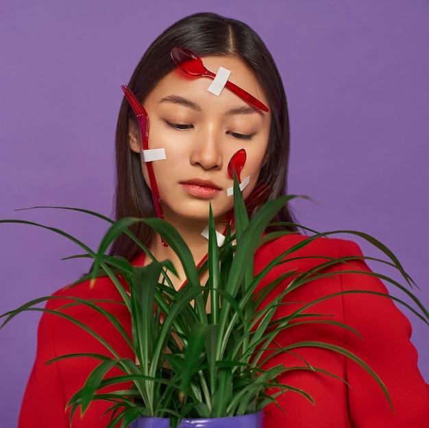 식물을 잡고있는 동안 플라스틱 숟가락으로 덮여있는 그녀의 얼굴을 가진 여자