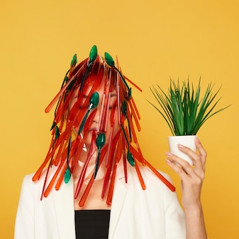 Woman having her face covered in red and green spoons and forks