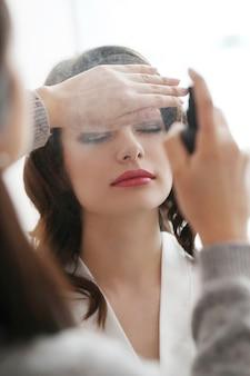 Женщина делает ее макияж, сделанный визажистом