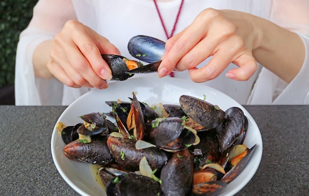 Woman having her steamed mussels in white wine by using an empty mussel shell to grab another mussel's meat out