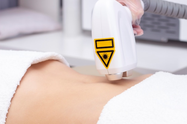 Woman having her stomach hair removed by female beautician. laser epilation treatment. close up