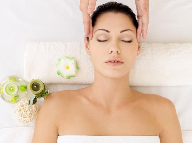 여자는 스파 살롱에서 얼굴 마사지를 데. 미용 치료 개념.