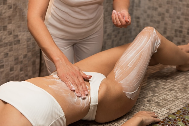 Woman having massage with cream at spa