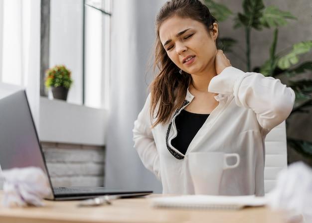 Donna che ha un mal di collo mentre si lavora a casa