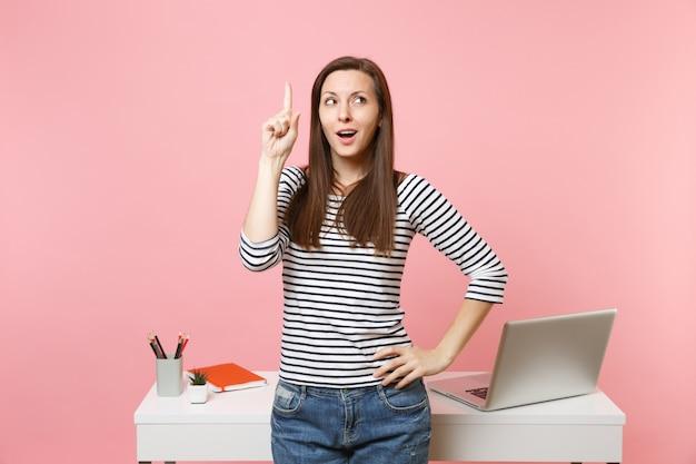 パステルピンクの背景に分離されたpcラップトップと白い机の近くに人差し指を上向きに考えて新しいアイデアを持っている女性。業績ビジネスキャリアコンセプト。広告用のスペースをコピーします。