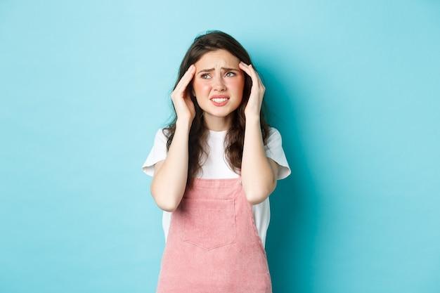 Donna con dolorosa emicrania, toccando la testa e accigliandosi, guardando l'angolo in alto a sinistra, soffrendo di mal di testa, in piedi su sfondo blu