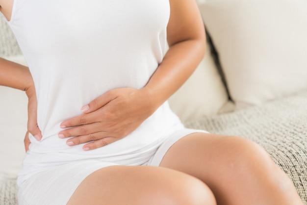 Женщина с болезненной болью в животе и боль в спине, сидя на диване у себя дома