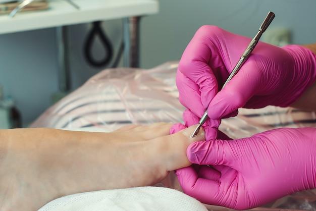 Женщина, имеющая педикюр в салоне. педикюр и уход за ногами. женщина расслабляется в салоне, заботясь о ногтях.