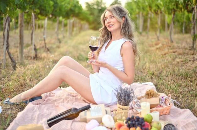 Donna che ha un picnic con un bicchiere di vino
