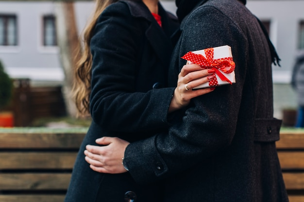 Woman having present and embracing with man
