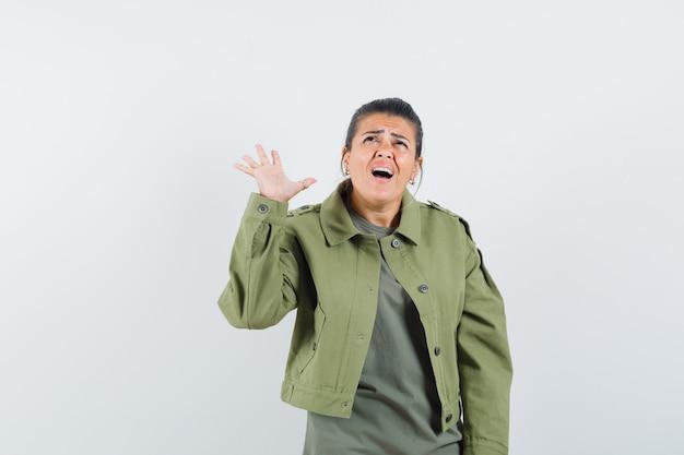 Donna che ha problemi con l'udito in giacca, t-shirt e sembra confusa