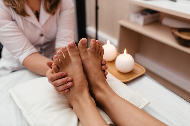 Woman having reflexology foot massage in wellness spa