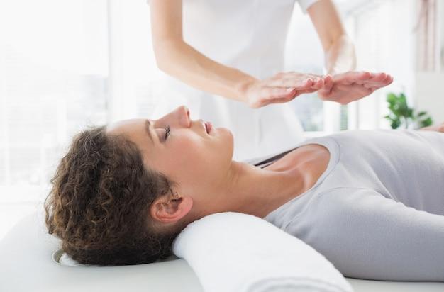 Женщина, имеющая лечение рейки