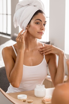 Woman having a relaxing day and using face cream