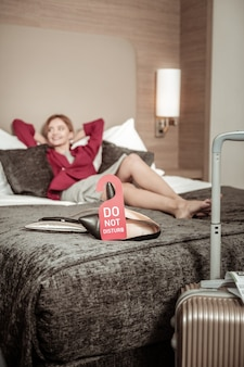 休んでいる女性。空港の後にホテルの部屋でベッドに横たわっている間休んでいるブロンドの髪の実業家