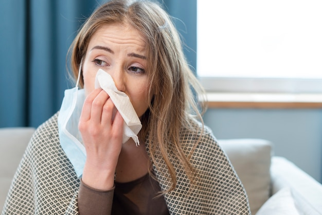 Woman having a runny nose indoors