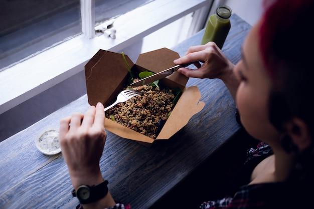 Donna che mangia un'insalata nella caffetteria
