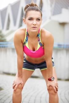 Woman having a short break while jogging