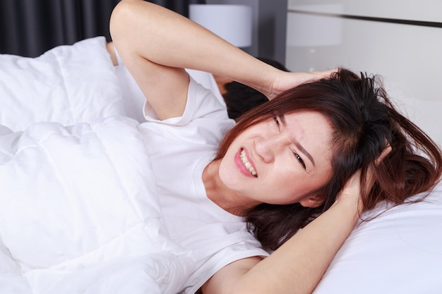 Woman having sleepless on bed and having migraine,stress, insomnia, hangover in bedroom