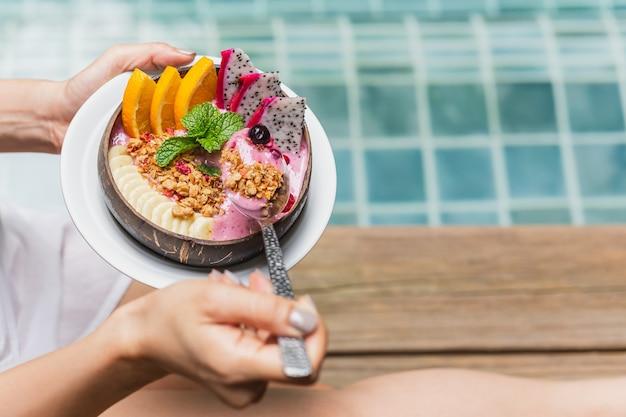 プールサイドでスムージーの朝食を食べている女性