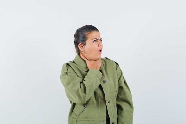 Woman having sore throat in jacket, t-shirt and looking unwell.
