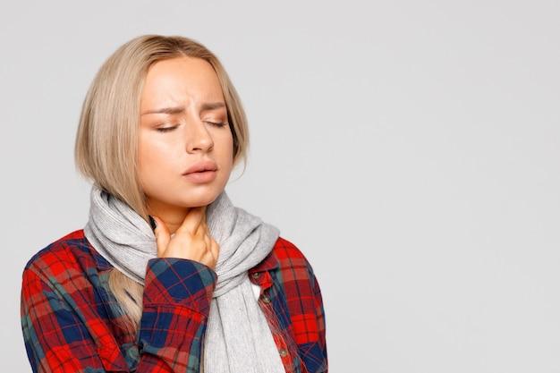 Woman having sore throat, throat pain