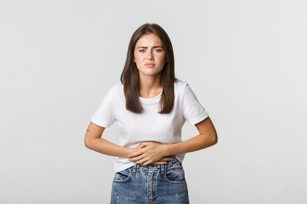 Woman having stomach ache, with hands on belly, discomfort from menstrual cramps. girl feeling nauseous.