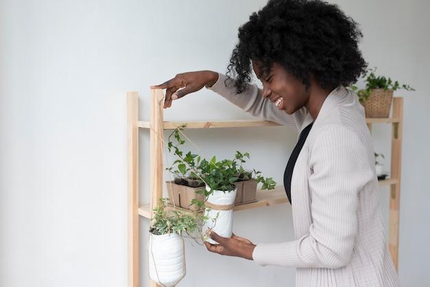 Donna che ha un giardino sostenibile in casa