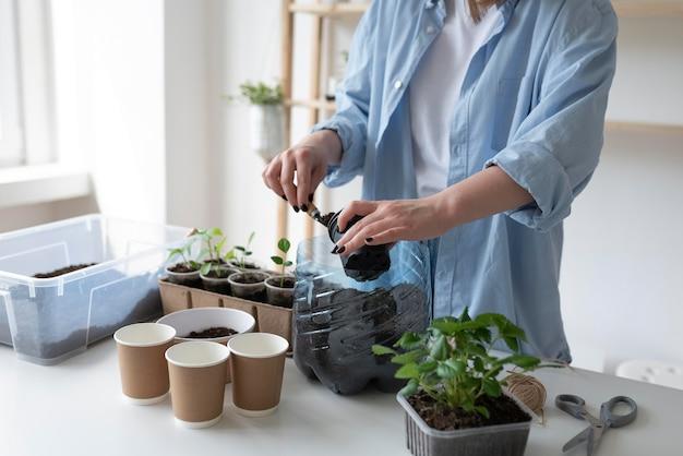 Donna che ha un giardino sostenibile in casa Foto Gratuite