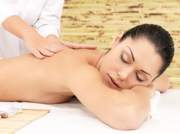 スパサロンで背中のセラピーマッサージを受けている女性。美容トリートメントのコンセプト。