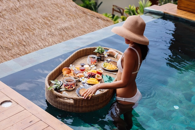 Женщина, имеющая тропический здоровый завтрак на вилле на плавающем столе