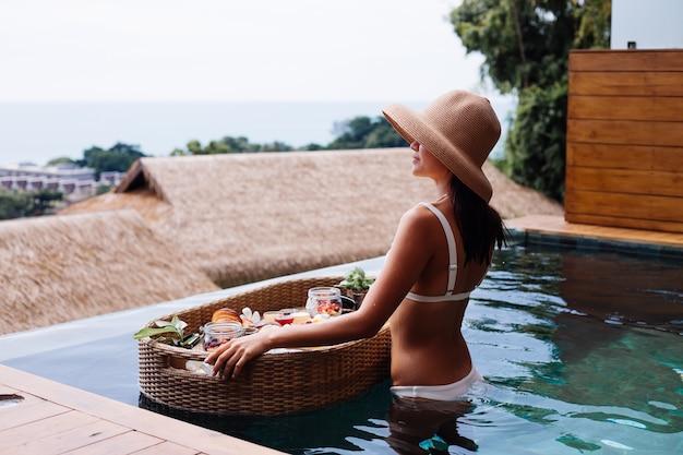 Donna che mangia colazione sana tropicale in villa sul tavolo galleggiante