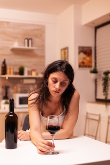 孤独とうつ病のためにアルコールを飲む不健康な行動をしている女性。アルコール依存症の問題で疲れ果てた不幸な人の病気と不安感。
